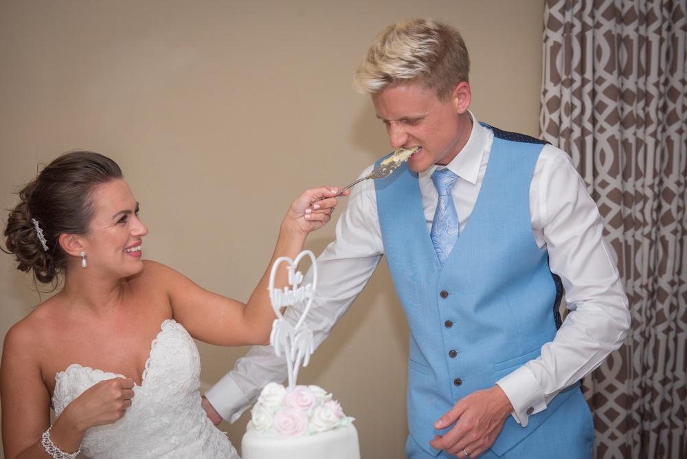 Wedding Cake Cutting Photo – Groom Eats the Cake